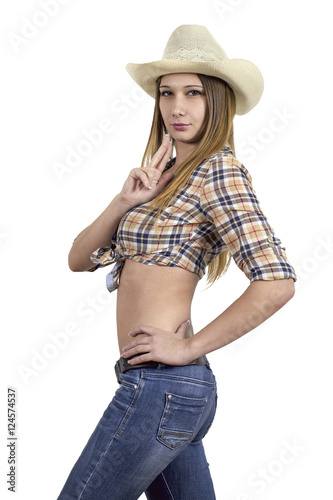 eb47a50e The young girl in a cowboy wearing a cowboy hat, jeans and a plaid shirt  mimics the firing of a gun. Isolated on white.