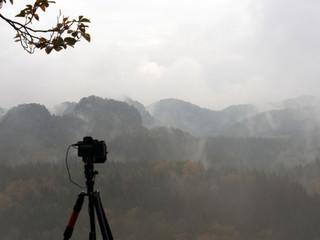 Kamera und Stativ vor bewölkter Landschaft