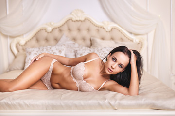 Perfect girl in a white sexy lingerie on vintage bed