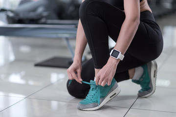 Active girl tying her shoelaces in a gym