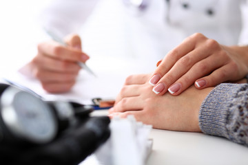 Friendly female doctor hold patient hand in office