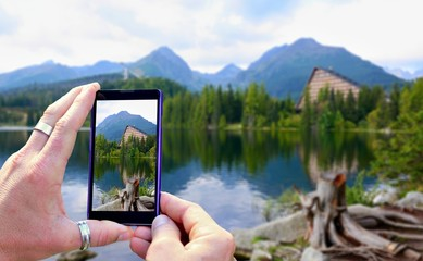 View over the mobile phone display during taking a picture of landscape in nature. Holding the mobile phone in hands and taking a photo. Focused on mobile phone screen.