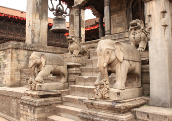 Ancient stone statue of elephants and dogs on steps in Bhaktapur