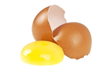 Broken egg with yolk and eggshell on white background
