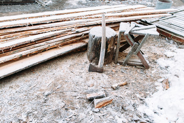 Firewood chopping workplace frosted by snow. Winter came to sawmill. Left outside tools in winter. Cold, early frosts, hoar concept