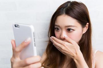 スマートフォン ・ 口をふさぐ女性