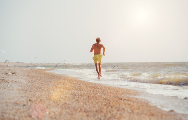 Man jogging on the desert sea line at the morning time