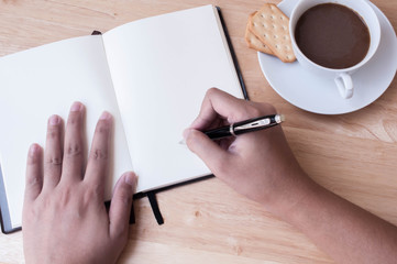 Writing in blank book on wooden table