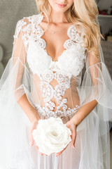 A portrait of a young bride in a lace underwear holding a huge white flower, blonde wavy hair on her shoulder
