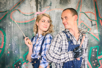 Young couple in overalls with tools. Concept of construction and home repair.