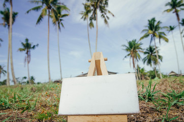 conceptual image white canvas and wooden easel over blurred back