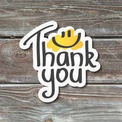 thank you, lettering with smile, handwritten text, paper sticker on realistic wood texture