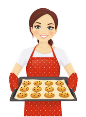 Smiling woman holding baking tray with homemade cookies wearing apron isolated