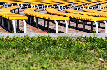 neat rows of green benches on a grass background
