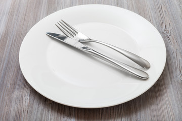 white plate with parallel knife, spoon on gray