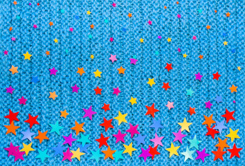 Colorful stars of different sizes on a blue knit background.