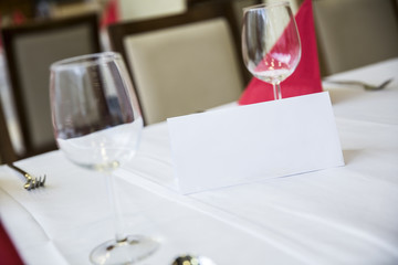 White tag line with two wine glasses on table in restaurant