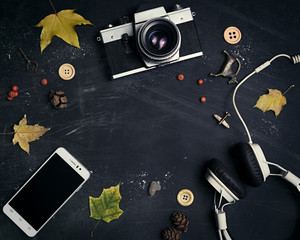 Composition of suede shoes, retro camera, headphones, mobile, yellow leaves on a dark, scratched background.  In the center of the free space for your design. Mock up for art work.