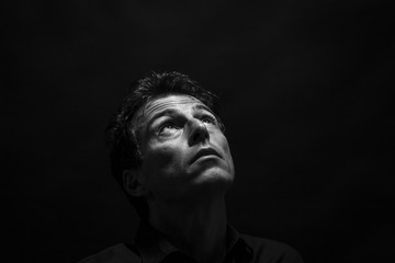 Isolated thinking man face looking up. Low key , black and white portrait.
