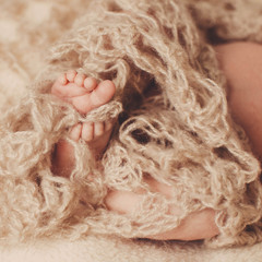 amazing  baby sleeps under a brown scarf
