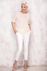 Blonde adult woman posing in studio.