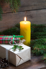 Christmas gifts and lighted candle with christmas tree and cones on wooden background