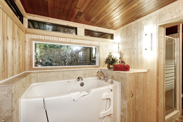 White bath tub in wooden paneled bathroom