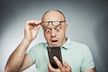 Middle-aged man looking at his mobile phone and he was surprised