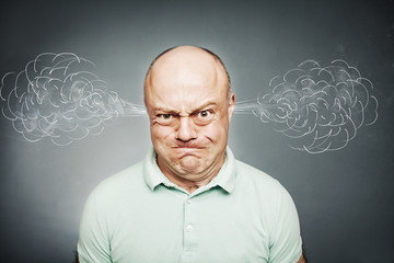 Closeup portrait of angry man, blowing steam coming out of ears,