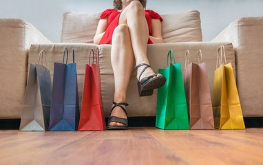 Shopping and consumerism concept. Legs of young woman sitting on sofa with colorful shopping bags.