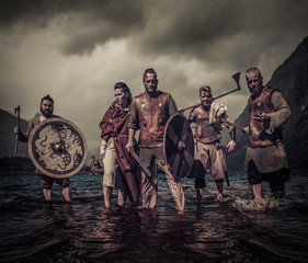 A group of armed Vikings standing on river shore