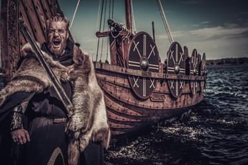 Viking warrior with sword standing near Drakkar on seashore