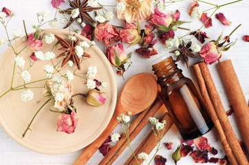 Essential oil of rose, cinnamon, anise mix. Herbal aroma beauty care. Dropper bottle, dried fragrant flowers, sticks, wooden utensils, top view background. Fototapete