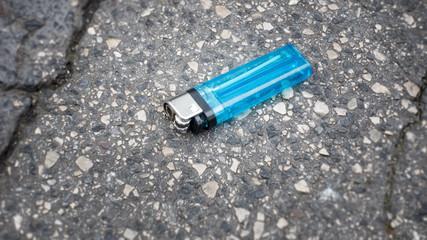 lost blue cigarette lighter at the asphalt