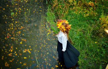 Beautiful young girl wearing a wreath of autumn leaves in a white shirt and black skirt enters the river. The view from the top. Horizontal orientation