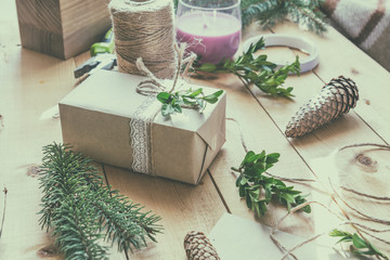 Wrapping eco Christmas packages with brown paper, string and natural branches and decor elements on wooden table