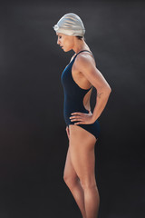 Professional female swimmer on black background