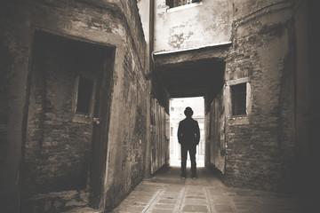 Man walking in a old mystic dark alley Wall mural