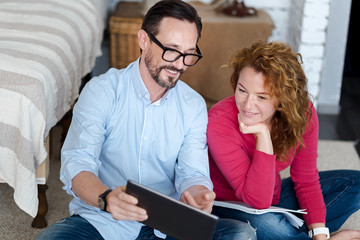 Middle-aged couple using tablet at home