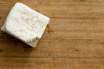 Cube of white cheese on cutting board