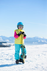 Smiling skier girl in winter resort