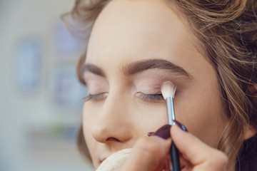 Make up artist doing professional eye makeup of young woman