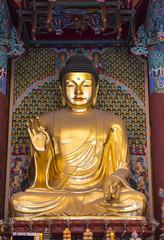 A big golden Buddha statue inside an ancient temple