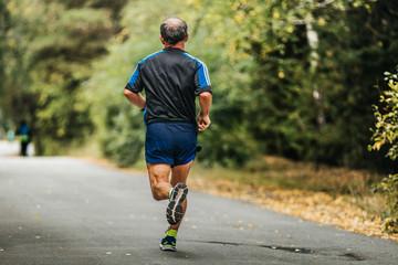 Wall Mural - active elderly man running down road in autumn Park