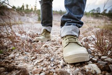 Foot of man walking on ground rock
