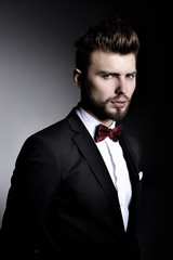 Portrait of handsome stylish man in elegant black suit and red b