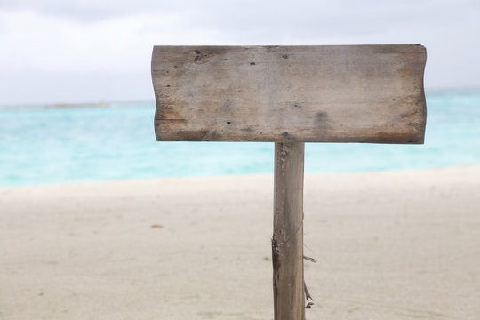 blank wood sign on the beach