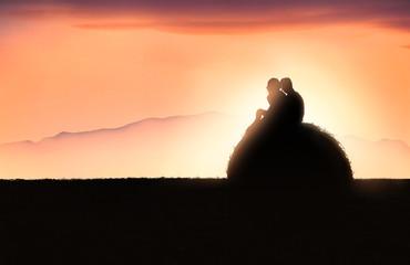 Silhouette di una giovane coppia sopra una balla di fieno al tramonto