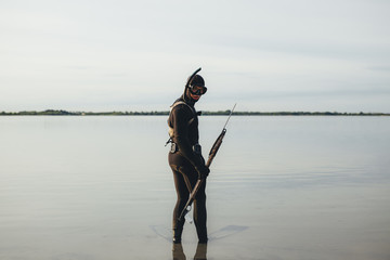 Spear fisherman standing in sea water looking over shoulder