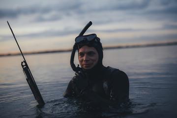 Happy underwater hunter with speargun